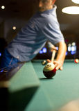 Pool shot. Young man shooting a tricky billiard shot at pool Stock Photos