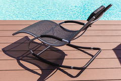 Pool side chaise lounge. A chaise lounge on the pool side made of wooden planks royalty free stock photos
