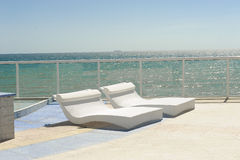 Pool side chaises by the sea Stock Images
