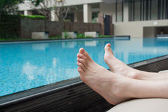 Pool side feet of someone taking a break on a holiday from swimming. Summertime calls for a break by the pool and relaxation near Royalty Free Stock Images