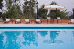 Pool-side lounge. Row of lounge chairs along a swimming pool stock images
