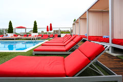 Pool side. With red chairs and blue water Royalty Free Stock Photo