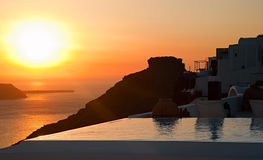 The pool, the Skaros rock silhouette and the sunset caldera view at Santorini Stock Photo