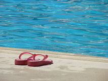 Pool slippers. Red slippers neat the pool Royalty Free Stock Image