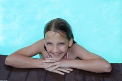 Pool Smiles. 12 year old girl on the edge of a swimming pool Royalty Free Stock Images
