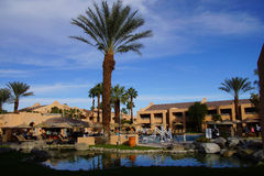 Pool and Southwestern style hotel. RANCHO MIRAGE, CALIFORNIA - DEC 20, 2014 - Pool and Southwestern style hotel buildings in green oasis with Palm trees, Rancho royalty free stock image