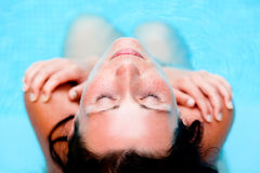 Pool sports. Playful pool vacations holiday woman relaxing embracing in water royalty free stock images