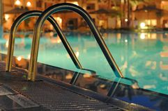 Pool stairs at night. A closeup of a hotel pool stair handles, with the hotel building lighted in orange in the distance Stock Image