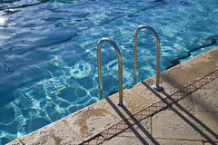 Pool Steps. Steps into a bright blue pool stock photography