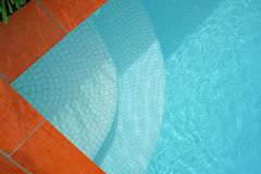 Pool Steps. Leading into a blue swimming pool royalty free stock images