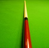 Pool stick on a pool table. Shallow depth of field. Focusing on the closer middle part of the stick Stock Image