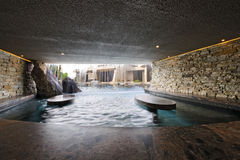 Pool With Stone Walls Against House. Modern swimming pool with stone walls against house Stock Photos