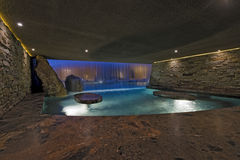 Pool With Stone Walls At Night. Modern swimming pool with stone walls against house at night Stock Photography