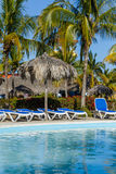 Pool, sun chairs and palm trees in an all inclusive hotel Royalty Free Stock Photography