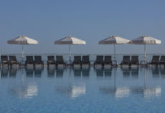 Pool sunbed. Sunbeds and umbrellas by the swimming pool on a sunny day Stock Photo