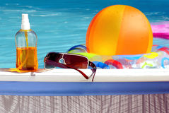 At the  pool. Suntan oil and sunglasses lying by the pool Stock Image