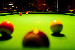 Pool table. A female pool player bending over the green table and ready to hit the white ball stock photography