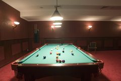 Pool table and balls. Close up of pool table and balls pictured mid game under billiard hall lights Stock Photography