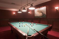 Pool Table/Billiards. Still-life of a pool table with balls and cues in a recreation room royalty free stock photo