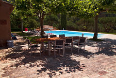 By the pool; Table and chairs in the shadow of Plane Trees Stock Photography
