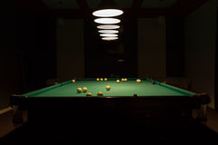 Pool Table in Dimly Lit Pool Hall Royalty Free Stock Photography