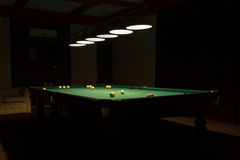 Pool Table in Dimly Lit Pool Hall. Billiard Balls Scattered on Pool Table in Empty Dimly Lit Pool Hall royalty free stock image