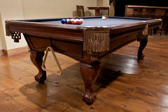 Pool table in finished basement. Beautiful wood pool table in home entertainment area with hardwood floors stock photography