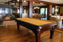Pool Table in the Living Room. A yellow felted pool table in a beautiful living room Royalty Free Stock Photography