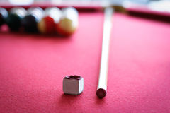 Pool Table, Stick and Chalk. A red felt pool table, pool balls ready for a game in the background, and a pool stick and chalk in focus stock photos