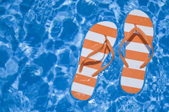Pool Thongs. Pretty pair of stripey flip flops or thongs in a sparkling blue swimming pool Stock Photo