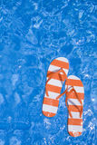 Pool Thongs. Pretty pair of stripey flip flops or thongs in a sparkling blue swimming pool with a man's feet Royalty Free Stock Photos