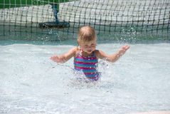 Pool time. Adorable little blond girl splashing in the pool Stock Image