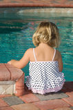 Pool time. Little blond girl sitting by the pool in a polka dot swimsuit stock images