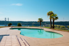 Pool to luxury waterfront house with palm trees and a view of Na Royalty Free Stock Photography