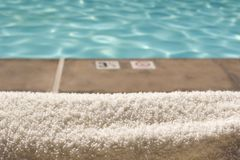 Pool Towel. A pool towel and a distant swimming pool Stock Photography