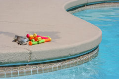 Pool toys. Goggles and diving sticks laying next to a pool royalty free stock photo