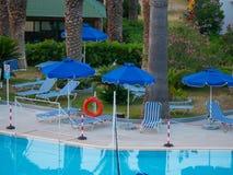 Pool Tropica leere Rettungsringstühle und -regenschirme stockfotos