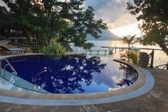 Pool am tropischen Strand bei Sonnenuntergang Stockfoto