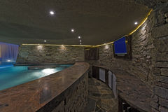 Pool With TV On Stone Wall. Modern swimming pool with flat screen television on stone wall Royalty Free Stock Images
