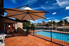 Pool and Umbrella. A pool bathed in sunshine in a Gold Coast waterfront home Stock Image
