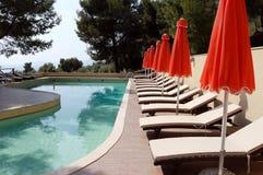 Pool und rote Regenschirme im griechischen Hotel Stockfoto