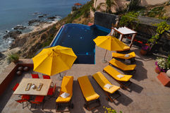 Pool view. Pool and yellow lounge chairs and umbrellas from above stock photography