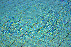 Pool water. Background of the clean surface of blue rippled swimming pool water which is so clear that you can look down to the ground royalty free stock photography