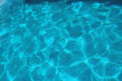 Pool water background. Cool blue water in a swimming pool with ripples and light reflections Royalty Free Stock Photography