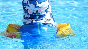 In the pool, in the water the child is swimming, in a sun cap and armbands, the view from the back. rays of the sun are. Reflected in the waves of water stock footage