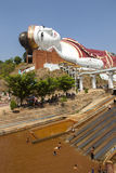 Giant Buddha and Recreation. A pool with water slides sits before a giant reclining Buddha image at Win Sein Taw Ya monastery near Mawlamyine in southern Myanmar royalty free stock photos