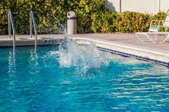 Pool water splashed after young boy jumping royalty free stock photography