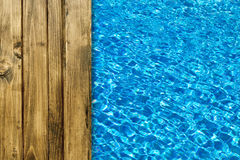 Pool water surface and wooden deck Royalty Free Stock Photography