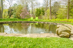 Pool of water in teh garden in garden. Pool of water in the garden with small fountain Royalty Free Stock Photo