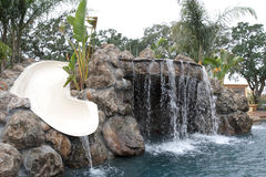 A pool with a waterfall in a luxury backyard Royalty Free Stock Image
